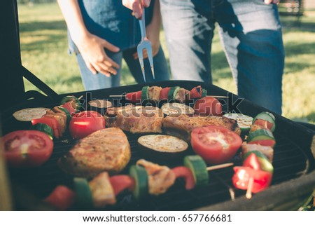 Friends making barbecue and having lunch in the nature. Couple having fun while eating and drinking at a pic-nic - Happy people at bbq party
