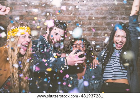 Friends making big party in the night. Four people throwing confetti and drinking champagne #481937281