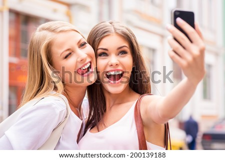 Friends making selfie Two beautiful young women making selfie and grimacing