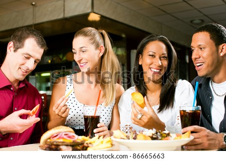 Friends - one couple is African American - eating hamburger and drinking soda in a fast food diner; focus on the meal
