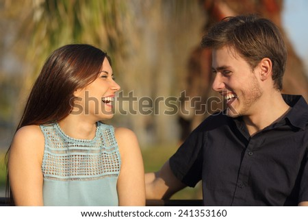 Friends or couple laughing and taking a conversation sitting on a bench in a park