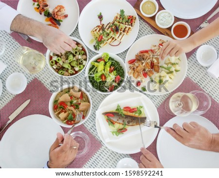 Friends or family eat lunch together. Various healthy fish and vegetables meals served on the table. Sharing a meal with others is the best form of quality time.