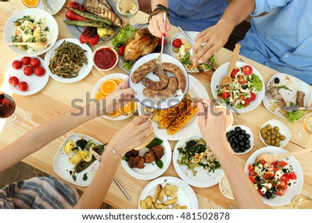 Friends passing plate with grilled sausages on picnic