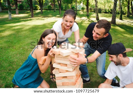 Friends playing board game outdoors.