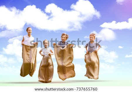 Friends playing sack race against blue sky