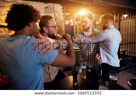 Friends preventing fighting of two angry guys in the bar.