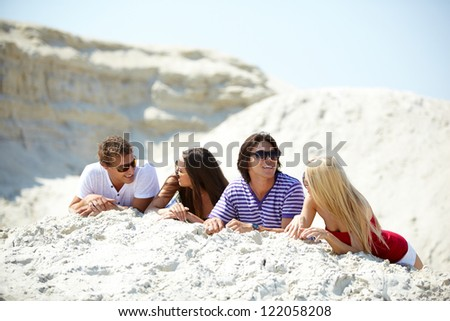 Friends resting on the sand and chatting with each other