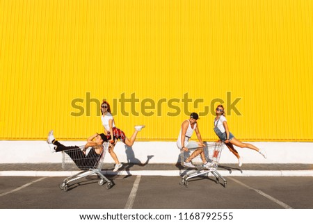 Friends ride on carts, near the supermarket, a great pastime, a group of young people rides on carts, couples in love have fun in Sunny weather, isolated space for text