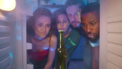 Friends run out of beer. View of four diverse friends opening steamy fridge finding one last bottle of beer. Young multiracial people lack alcohol at home party