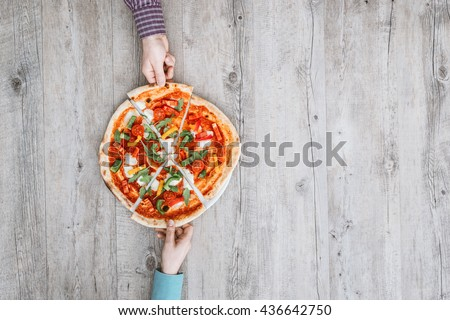 Friends sharing a delicious pizza on a rustic table, they are holding a slice, top view