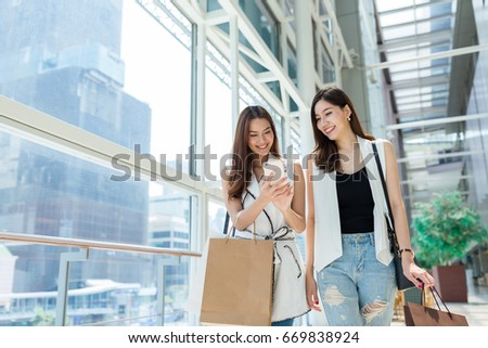 Friends shopping together and using mobile phone