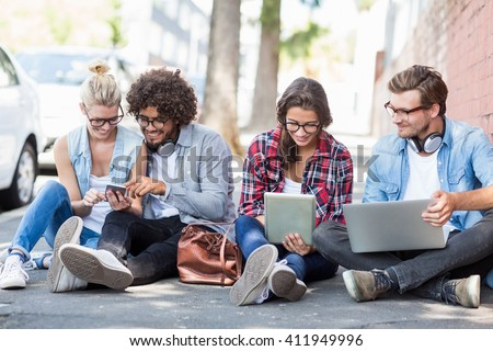 Friends sitting on roadside using mobile phone, digital tablet and laptop
