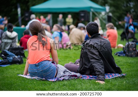 Friends sitting on the grass, enjoying an outdoors music, culture, community event, festival.