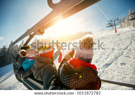 friends skiers and snowboarders on ski lift in the mountain at winter vacations back view Stock photo ©