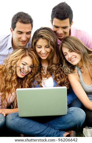 Friends social networking on a laptop computer outdoors