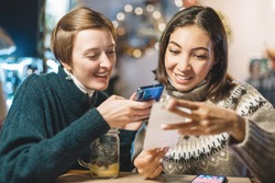 Friends split the bill using the app on their smartphone after a delicious dinner in a cafe.