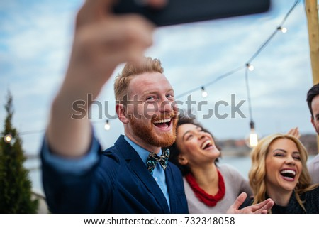 Friends taking a photo with mobile phone.