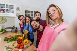 Friends taking a selfie in the kitchen wearing green beans stalks under their noses while standing in front of table full vegetables and pasta