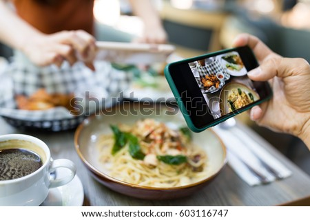 Friends taking photo on dish in restaurant