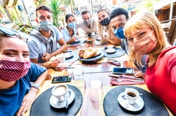 Friends taking selfie at coffee bar - New normal lifestyle concept with young people having fun together at restaurant cafe covered by face masks - Bright vivid filter