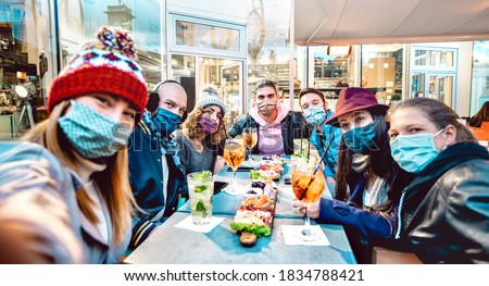 Friends taking selfie outside at cocktail bar - New normal lifestyle concept with young people having fun together at restaurant cafe covered by face masks - Vivid filter with focus on central guy