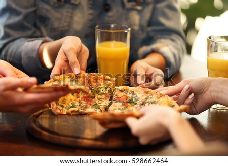 Friends taking slices of tasty pizza from plate, close up view