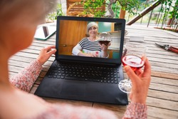 Friends talking in video call with device at distance in lockdown and quarantine from Covid-19 Coronavirus - Friendly women drinks red wine toasting online with laptop - Concept of prevention security