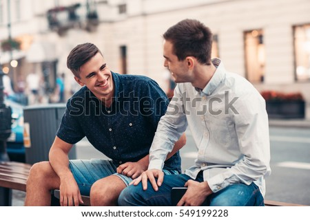 Friends talking together on a bench in the city