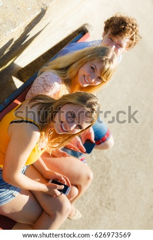 Friends texting using mobile phones outdoor. Young women and man browsing internet on smartphone. Summer relax. #626973569