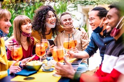 Friends toasting drinks at cocktail bar with face mask - New normal life concept with happy people having fun together drinking spritz at restaurant - Vivid filter with focus on black hair woman