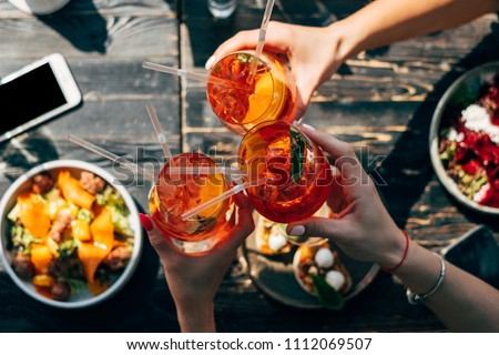 Friends toasting each other with aperol spritz cocktails at the dinner table, top view