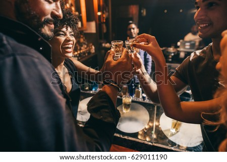 Friends toasting each other with shots of vodka as they enjoy a relaxing night out together at the pub. Group of friends together having fun