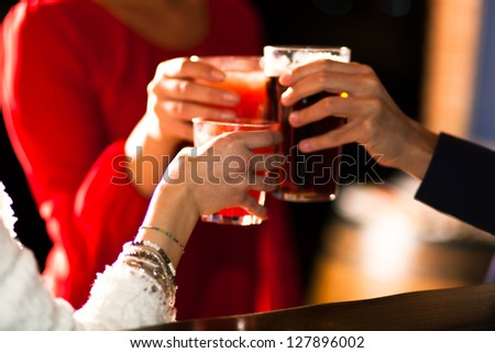 Friends toasting glasses in a pub