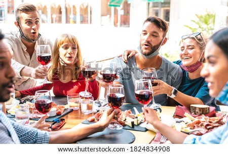 Friends toasting red wine at restaurant bar wearing opened face masks - New normal lifestyle concept with happy people having fun together on sunny day - Bright filter with focus on left blond woman Stockfoto ©