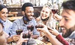 Friends toasting red wine glasses at outdoor restaurant bar with open face mask - New normal lifestyle concept with happy people having fun together on warm filter - Focus on afroamerican guy