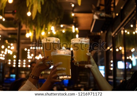 Friends toasting with glasses of beer at the pub brewery beautiful bokeh on Oktoberfest. Happy friend drinking, talking and clinking glasses at bar or pub.Leisure, friendship and communication concept