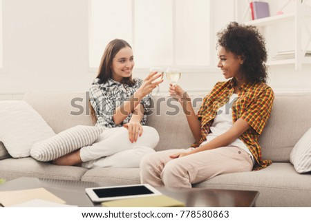 Friends toasting with wineglasses. Two young women cheering with wine, chatting and celebrating new life, slumber party, copy space
