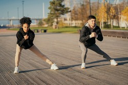 friends trainers muscle stretching Man and woman African American in sports comfortable clothing for aerobics fitness training on the waterfront in the city. couple playing sports in the Park