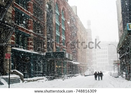 Friends travel down a New York City street in a blizzard #748816309