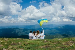 Friends travelers Men and Women sitting on cliff with national flag mountains and clouds aerial view Love and Travel happy emotions Lifestyle concept. traveling active adventure vacations Ukraine
