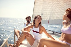 Friends traveling together on vacation. Smiling people and men sailing on yacht.