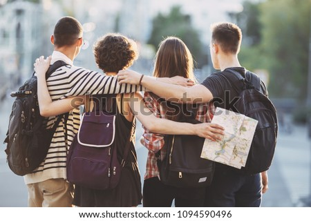 Friends traveling, togetherness, sightseeing concept. Young people with backpacks and map on city background #1094590496