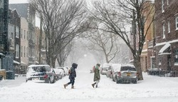 Friends trek through a snow covered street in Brooklyn during a blizzard.