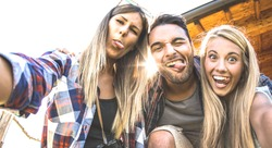 Friends trio taking selfie at trekking excursion - Happy friendship and freedom concept with young millenial people having fun together with funny faces on outdoors experience - Warm backlight filter