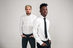 Friends. Two guys in white shirts and dark pants posing in the studio on a white background