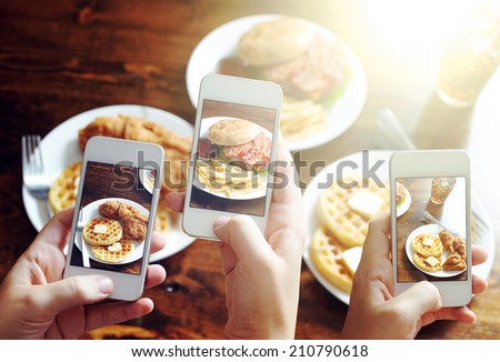friends using smartphones to take photos of food with instagram style filter
