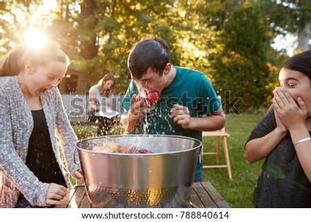 Friends watch teenage boy apple bobbing at garden party