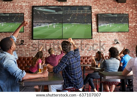 Friends Watching Game In Sports Bar On Screens Celebrating #637107007