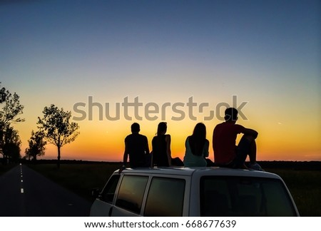 Friends watching sunset on a car