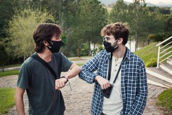 Friends wearing face mask  greeting each other with elbow in the street. Avoid the spread of coronavirus, social distance and friendship concept. The new normal. Safety measures and health care.